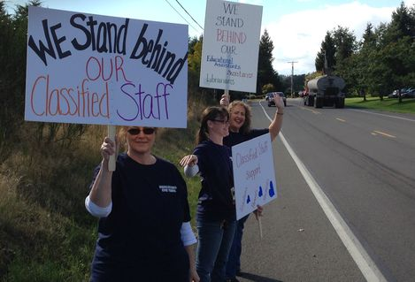 "A picketter holds a sign reading ""We stand behind our classified staff"""