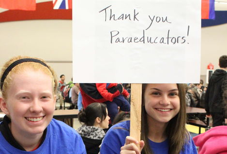 "Two students sit while holding a sign that reads ""Thank you paraeducators."""