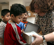 A WEA Children's Fund donor hands out shoes to students.